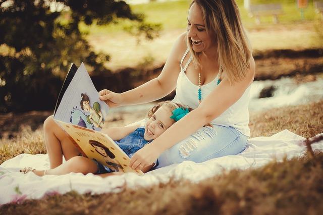 Máma čte dceři knížku pro děti
